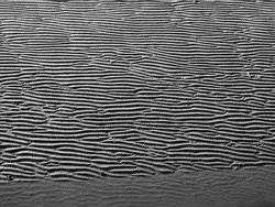 A full frame grey beach background with wavy pattered surface and water running in a line though the wet sand