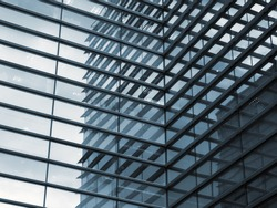 a full frame modern urban office architectural abstract with geometric shapes and buildings reflected in blue glass windows