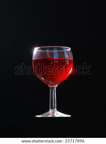 A full glass of red wine on black background.
