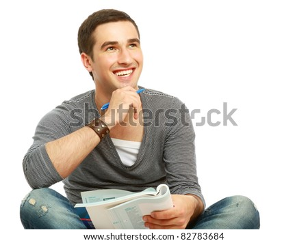A full-lenght portrait of a young handsome college guy sitting on the floor and studying, isolated on white