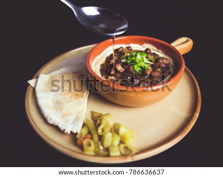 A full length color studio image of Egyptian, Arabian, Middle Eastern Traditional food (Fava Beans with Tahini, oil, green paprika  ) A.K.A (Foul) - Also served in Lebanon and Arabian countries. #786636637
