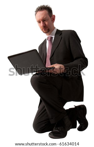 A full length of a mid thirties business man.  The man is kneeling down and using a black laptop computer.  Studio isolated on a white background.
