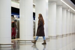 A full-length photo of a woman in a medical face mask to avoid the spread of coronavirus who is going on the subway platform. A girl in a surgical mask is keeping social distance on a metro station.