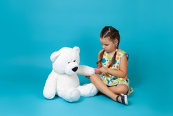 a full length portrait of a girl sitting cross legged on the floor pulling a splinter out of a white teddy bear's paw with tweezers isolated on a blue background.