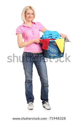 A full length portrait of a young woman carrying a full laundry basket isolated on white background