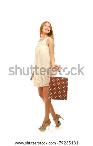 A full-length portrait of a young woman with shopping bags, isolated on white