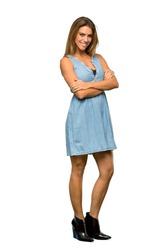 A full-length shot of a Blonde woman with jean dress with arms crossed and looking forward over isolated white background