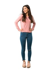 A full-length shot of a Teenager girl with pink shirt posing with arms at hip and laughing