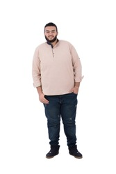 A full-length shot of an unfitness young man standing hands in pocket wearing a shirt and jeans, isolated on a white background.
