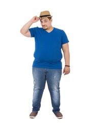 A full-length shot of an unfitness young man wears a hat and jeans, tight blue t-shirt, isolated on a white background.