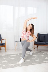 A full-length young fit woman in gray leggings with her legs spread wide leans sideways in a home interior with a large white window.