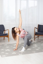 A full-length young fit woman in gray leggings with her legs spread wide makes twists in a home interior with a large white window.