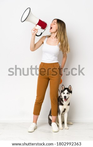 A full length young pretty woman with her dog shouting through a megaphone
