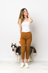 A full length young pretty woman with her dog thinking an idea