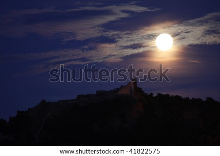 A full moon is above a castle
