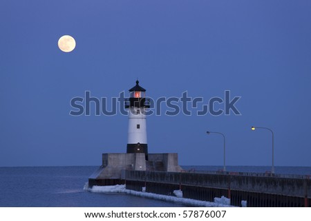 A full moon rising over lighthouse on Lake Superior.