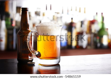 A full mug of beer with bottle and cap shot in bar