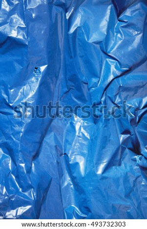 A full page of bright blue plastic refuse sack material background texture