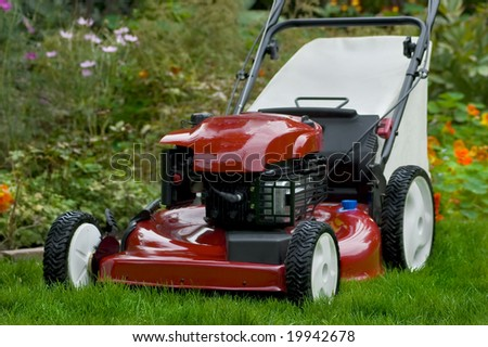 A full shot of a red lawnmower.