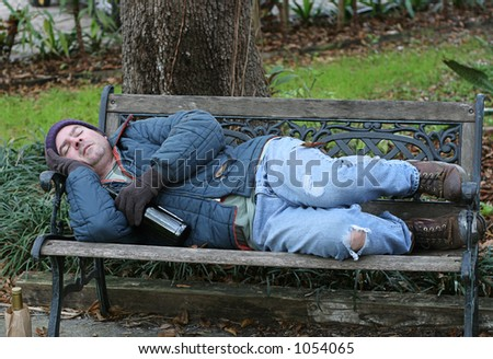 A full view of a homeless man asleep on a park bench with his wine bottle.