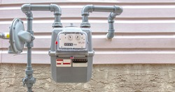A full view of a residential urban natural gas meter measuring gas consumption, outside house gas meter