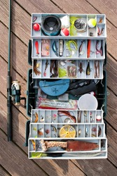 A fully stock fisherman's tackle box rod and reel ready for a long day of fishing.