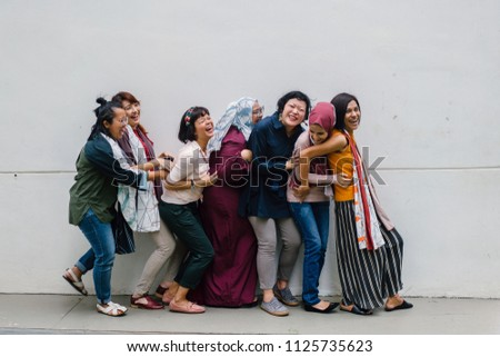 A fun and light hearted group portrait of a diverse team of women from different cultures and ethnicities. They are standing close to one another and tickling each other and laughing and having fun. #1125735623