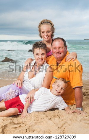 A fun family being photographed on the beach.