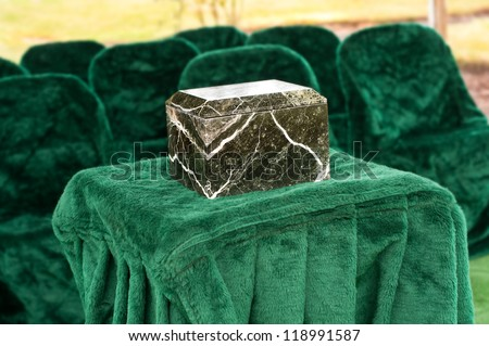A Funeral Service Scene with a Marble or Granite Urn placed on a Table in front of chairs outside at the gravesite.