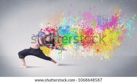 A funky contemporary hip hop dancer dancing in front of grey background with colorful bright paint splatter concept #1068648587