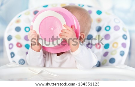 A funny baby is eating from pink plate