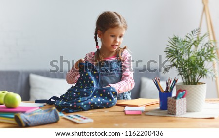 a funny child  girl  doing homework writing and reading at home