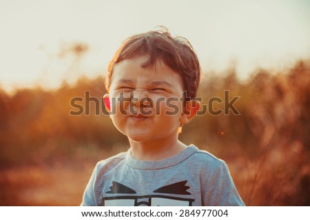 A funny face of a two years boy in the sunset lights on a summer day. #284977004