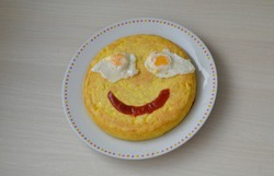 A funny face on a spanish omelette as an example of funny food and cooking for kids