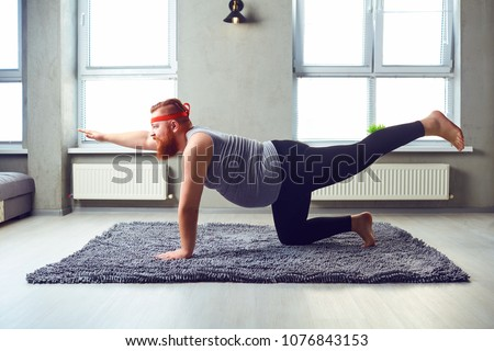 A funny fat bearded man in sports clothes does yoga in the room.