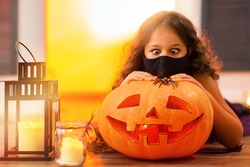 A funny girl looks with surprise at a spider on an orange pumpkin