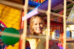 A funny girl sits in a playground with soft and bright equipment and throws colorful balls towards the camera while enjoying the warm summer sun