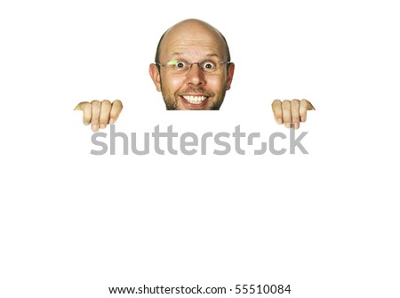 A funny happy smiling man holding a white sign or looking up from behind white wall