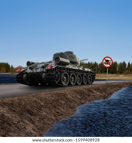 """A funny image of a tank having stopped on the coast road before the """"no tanks"""" traffic sign with stop lights on. Copy space on the upper and lower part of the photo."""