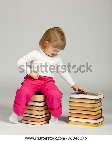 A funny little girl sitting on a stack of books and touching a book; neutral background
