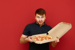 A funny man with a beard holds a pizza box in delivery and looks into the camera with a hungry lustful face. Portrait of hungry man with pizza box on red background. Fast junk food concept.