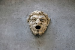 A funny open-mouthed gargoyle on a wall or door in Bergamo, Italy