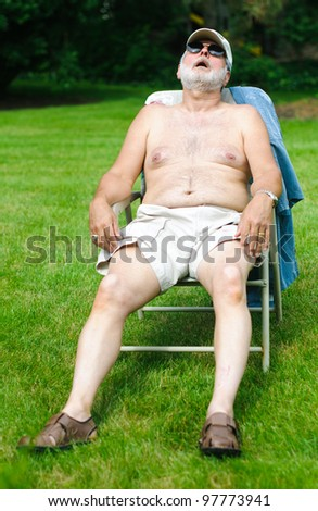 A funny picture of an older shirtless man sleeping in a folding chair.