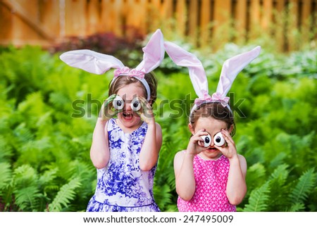 A funny portrait of two girls having fun on Easter wearing bunny ears and holding up silly eyes made from eggs outside in a garden during the spring season.  Part of a series.
