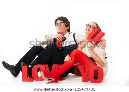 A funny young couple holding red letters love celebrating Valentines Day