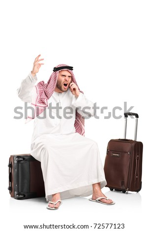 A furious arab shouting on a mobile phone seated on his luggage isolated on white background