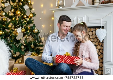 A futher gining a crtistmas present to his happy daughter in front of the fir-tree with candles. New year's eve. Christmas eve. Cozy holiday at the fir-tree with lights and gold decor. #755722783