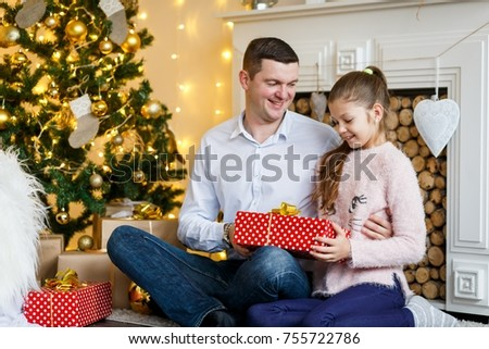 A futher gining a crtistmas present to his happy daughter in front of the fir-tree with candles. New year's eve. Christmas eve. Cozy holiday at the fir-tree with lights and gold decor. #755722786