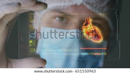 A futuristic physician, a surgeon, examines a technological digital holographic plate, a medical mask, a cap, brown eyes. Concept: futuristic medicine, new technologies, doctors, laboratory, future. #651550963
