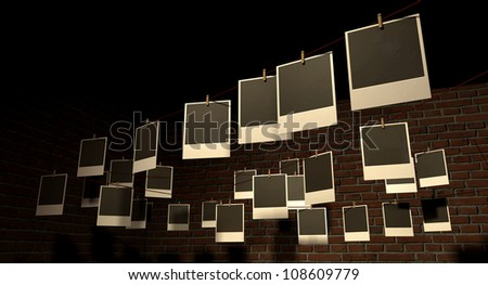 A gallery of blank polaroids pegged onto multi-directional red strings in front of a face brick wall